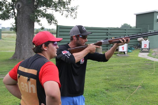 Brad Kidd of Stuart, Florida, a national champion in sporting clays, gives instruction to a member of the Marquette University High School trapshooting team during a workshop at Waukesha Gun Club in Waukesha, Wisconsin.