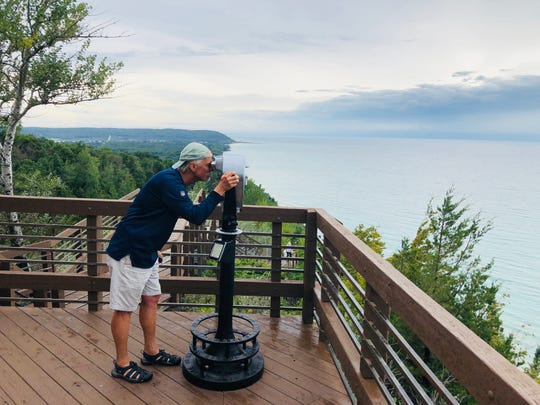 Writer Brian Clark peers through a pair of big binoculars at Lake Michigan from the Inspiration Point/Arcadia Overlook in Manistee County north of Ludington in Michigan.