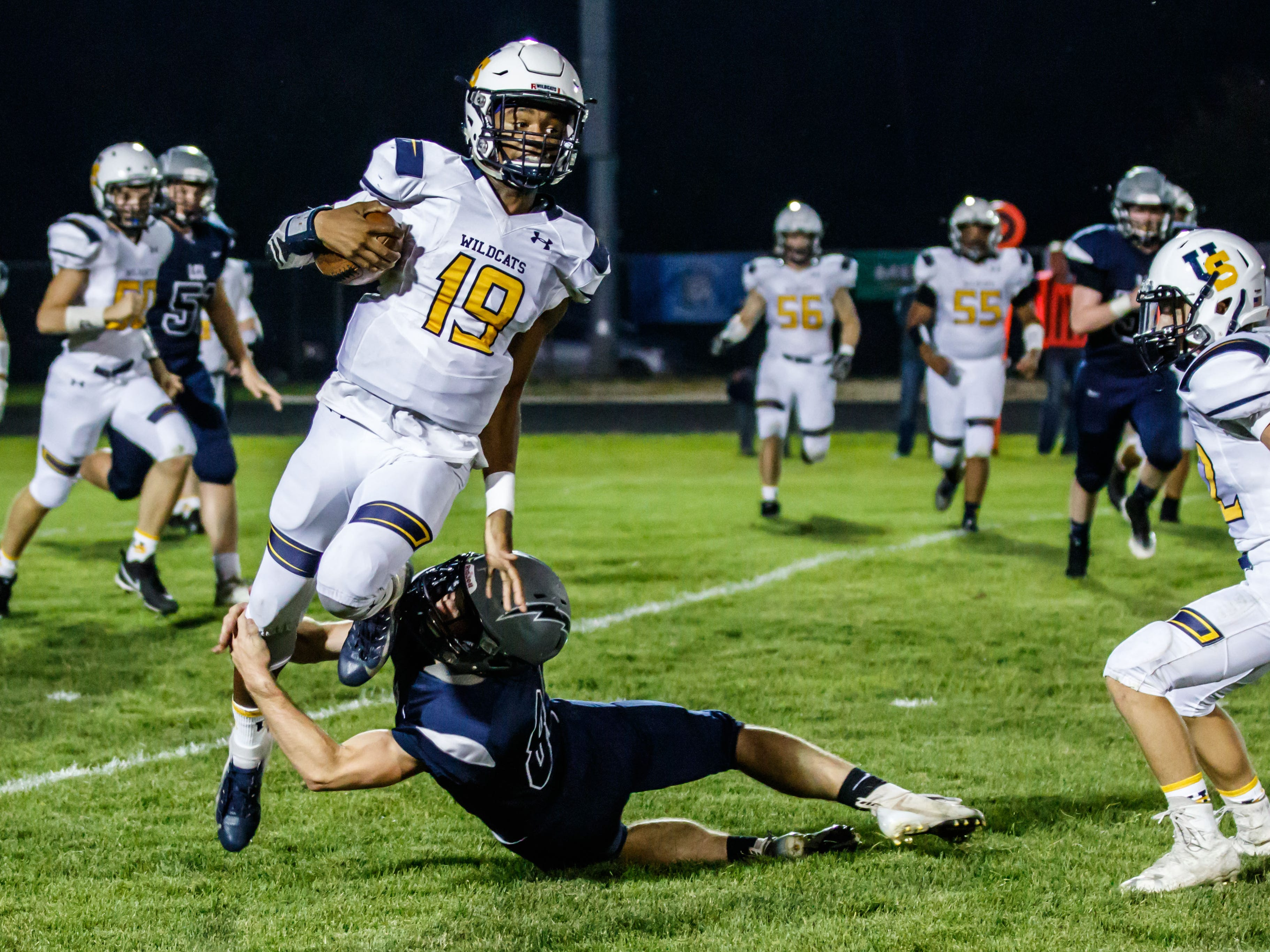 University School quarterback CJ Boyd (19) slips a tackle by Lake Country Lutheran's Jonathan Buschke (84) during the game at Lake Country Lutheran on Thursday, Sept. 13, 2018.