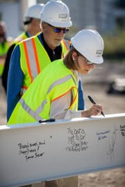 Donna Baumgartner signs a steel beam for the Milwaukee Ballet's new school and rehearsal facility, while her husband Donald looks on. The Baumgartners have donated $10 million for the new structure at 132 N. Jackson St., which will be called the Baumgartner Center for Dance.