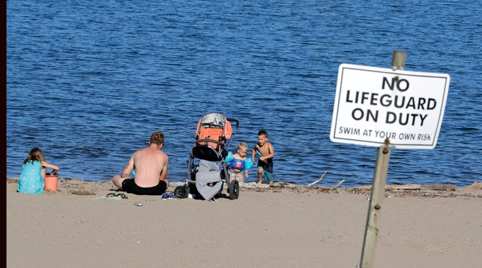 Ben Hall and his three children play in the sand and water at South Shore Park beach on Thursday. The beach is frequently closed to swimming due to bacterial contamination of the water but the Milwaukee Health Department stops posting water quality advisories after Labor Day.