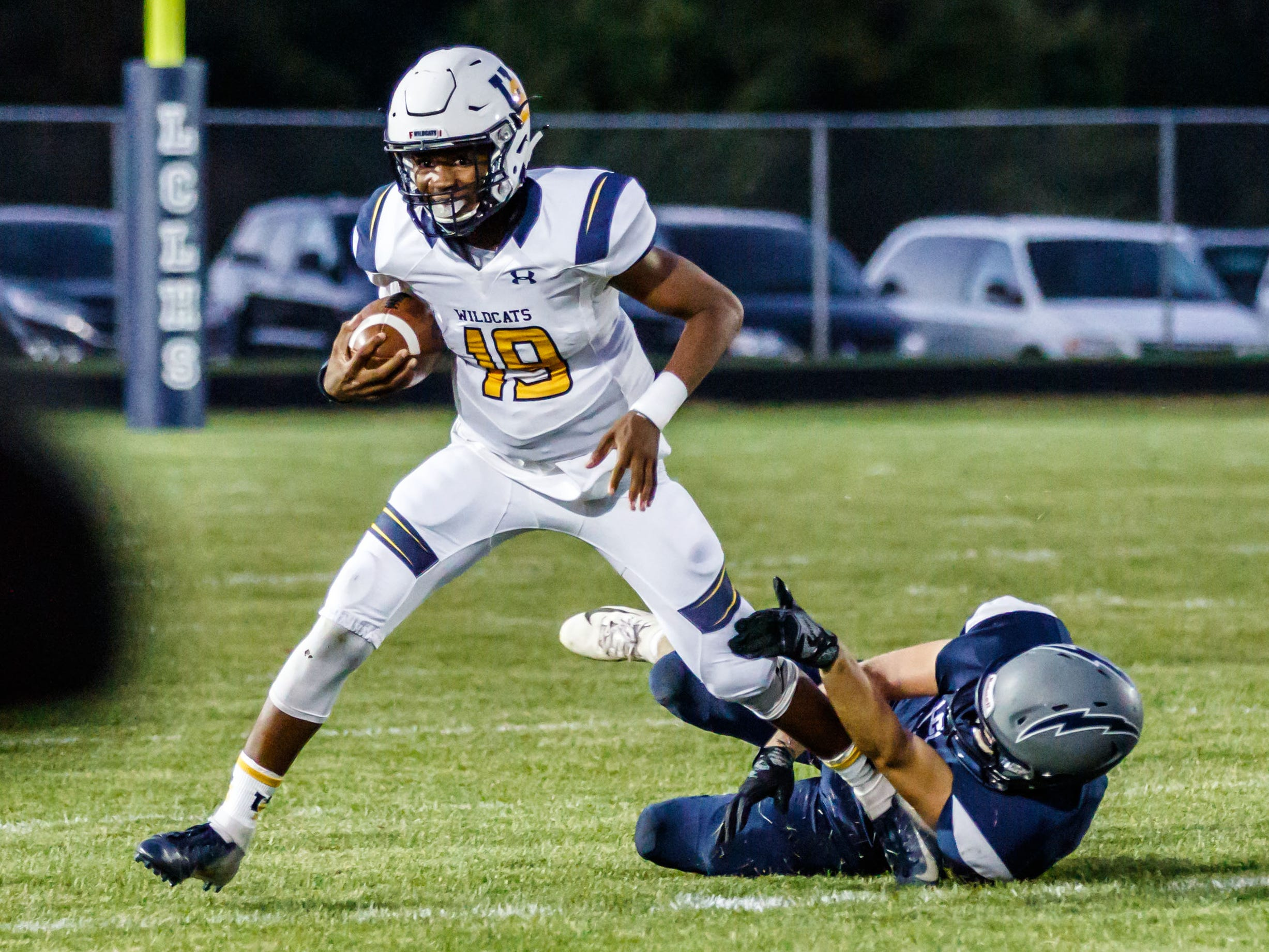 University School quarterback CJ Boyd (19) gets caught in the backfield by Lake Country Lutheran's Andrew Schumacher (20) during the game at Lake Country Lutheran on Thursday, Sept. 13, 2018.