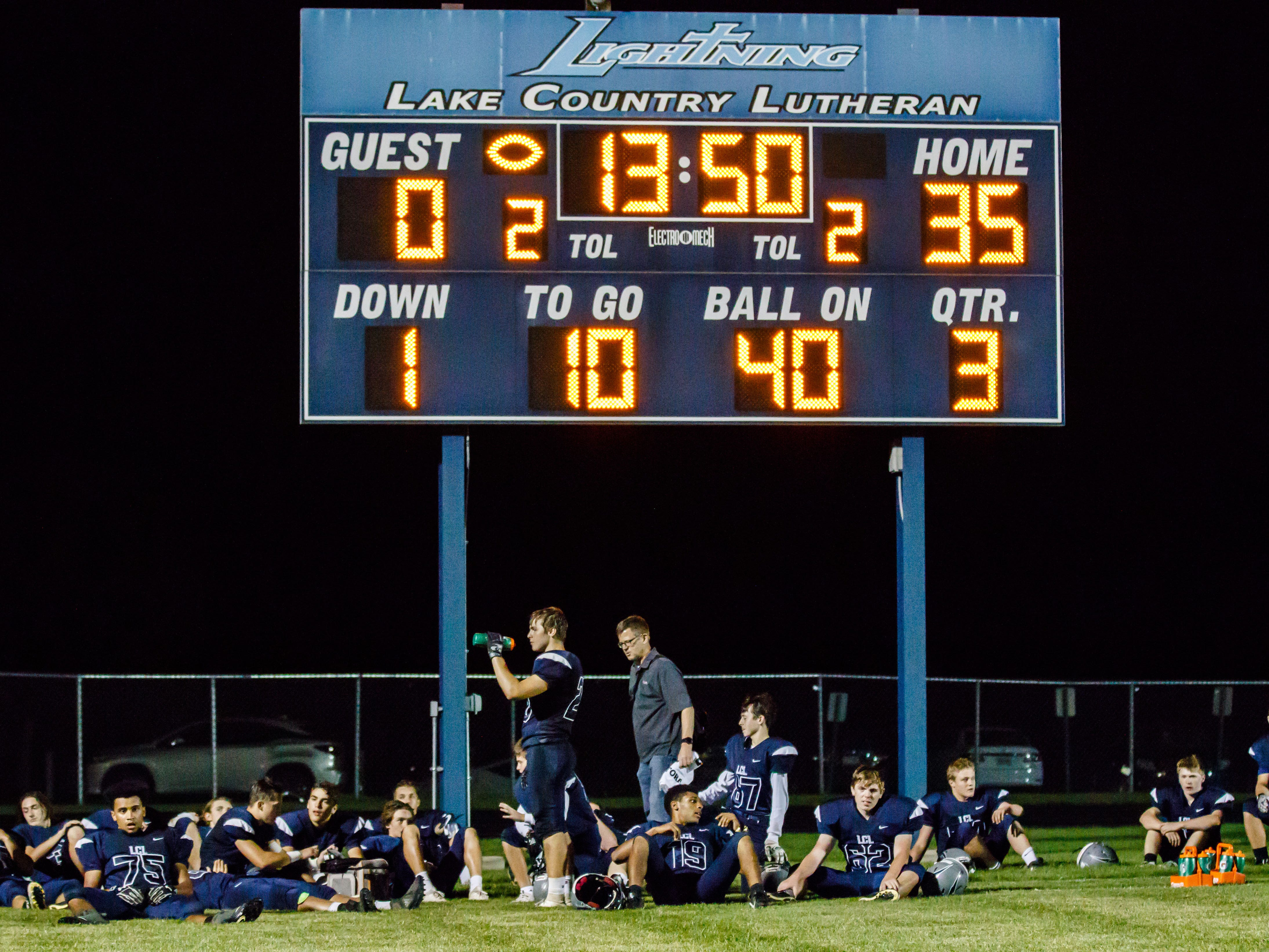 Lake Country Lutheran players rest under the scoreboard during halftime of the game at home against University School of Milwaukee on Thursday, Sept. 13, 2018.