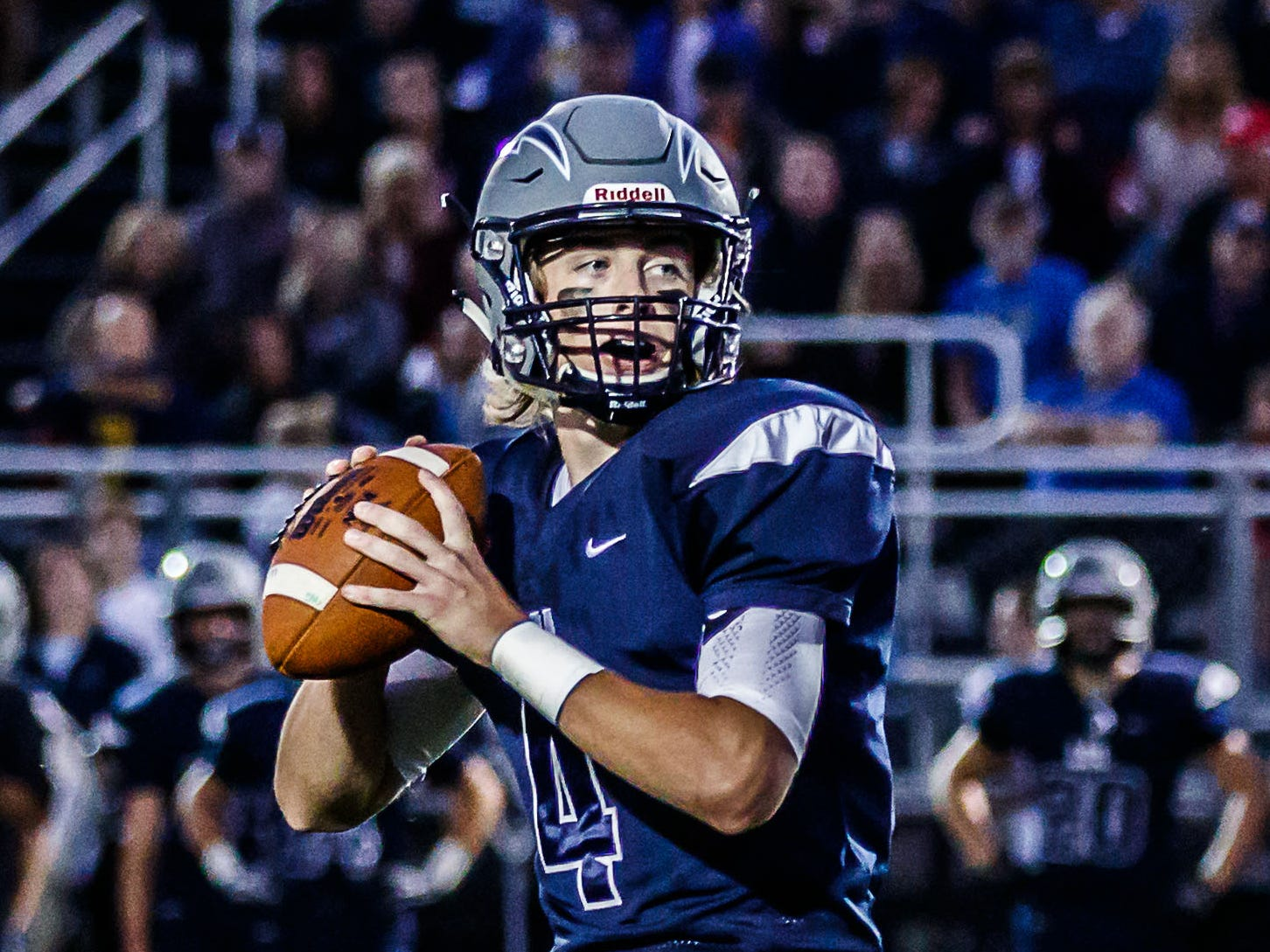 Lake Country Lutheran quarterback Ethan Wilkins (4) drops back to pass during the game at home against University School of Milwaukee on Thursday, Sept. 13, 2018.