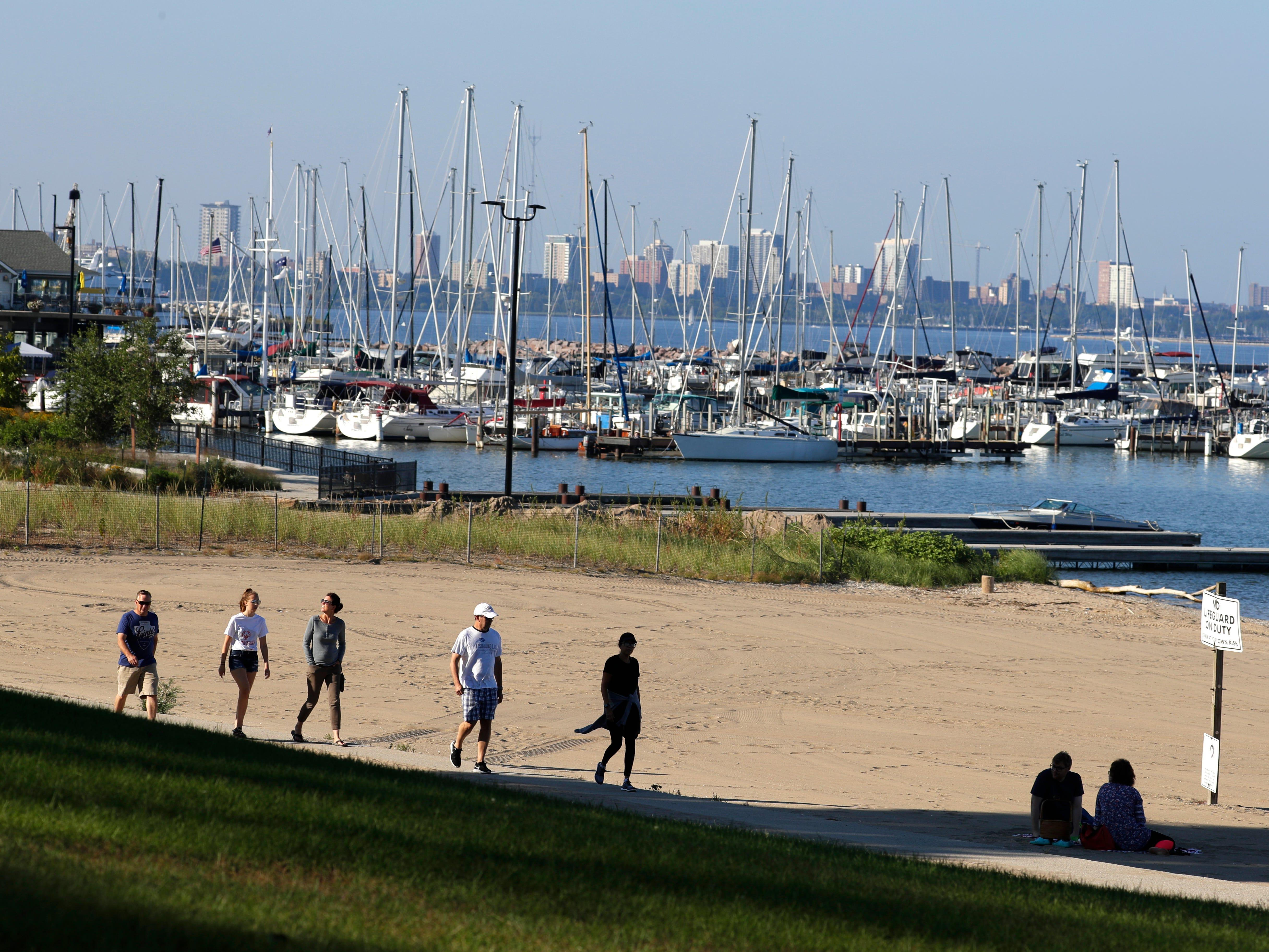 South Shore Park visitors walk past the public beach south of the South Shore Yacht Club.