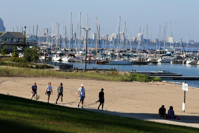 South Shore Park visitors walk past the public beach south of the South Shore Yacht Club.