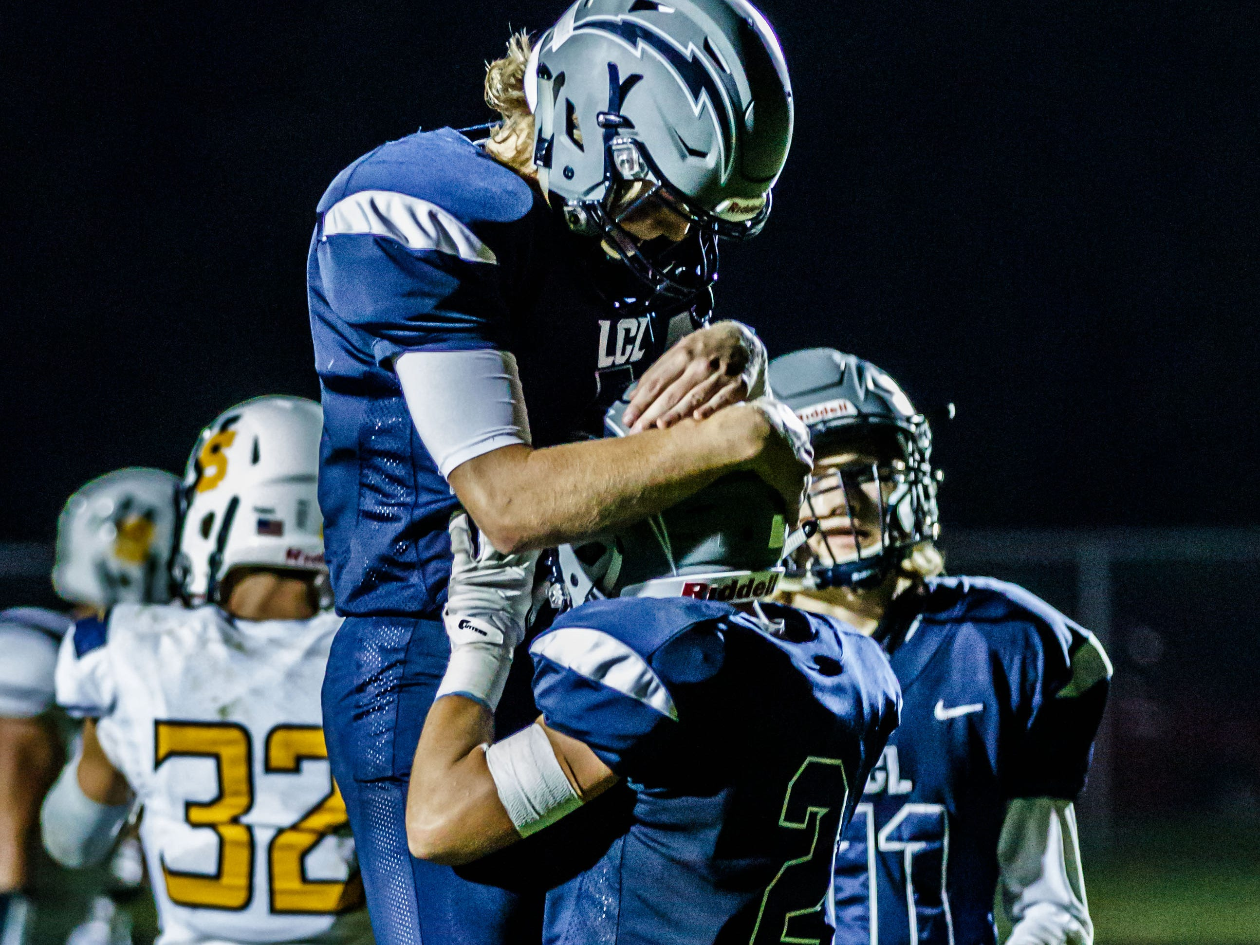 Lake Country Lutheran quarterback Ethan Wilkins (left) celebrates a touchdown with receiver Will Brazgel (2) during the game at home against University School of Milwaukee on Thursday, Sept. 13, 2018.