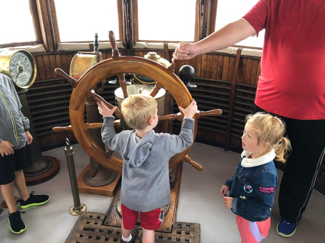 Children, under the watchful eye of their father, investigate the wheelhouse of the City of Milwaukee railroad car ferry, which plied the waters of Lake Michigan for more than half a century.  Now docked in Lake Manistee in western Michigan, it serves as a B&B, museum ship and event venue.
