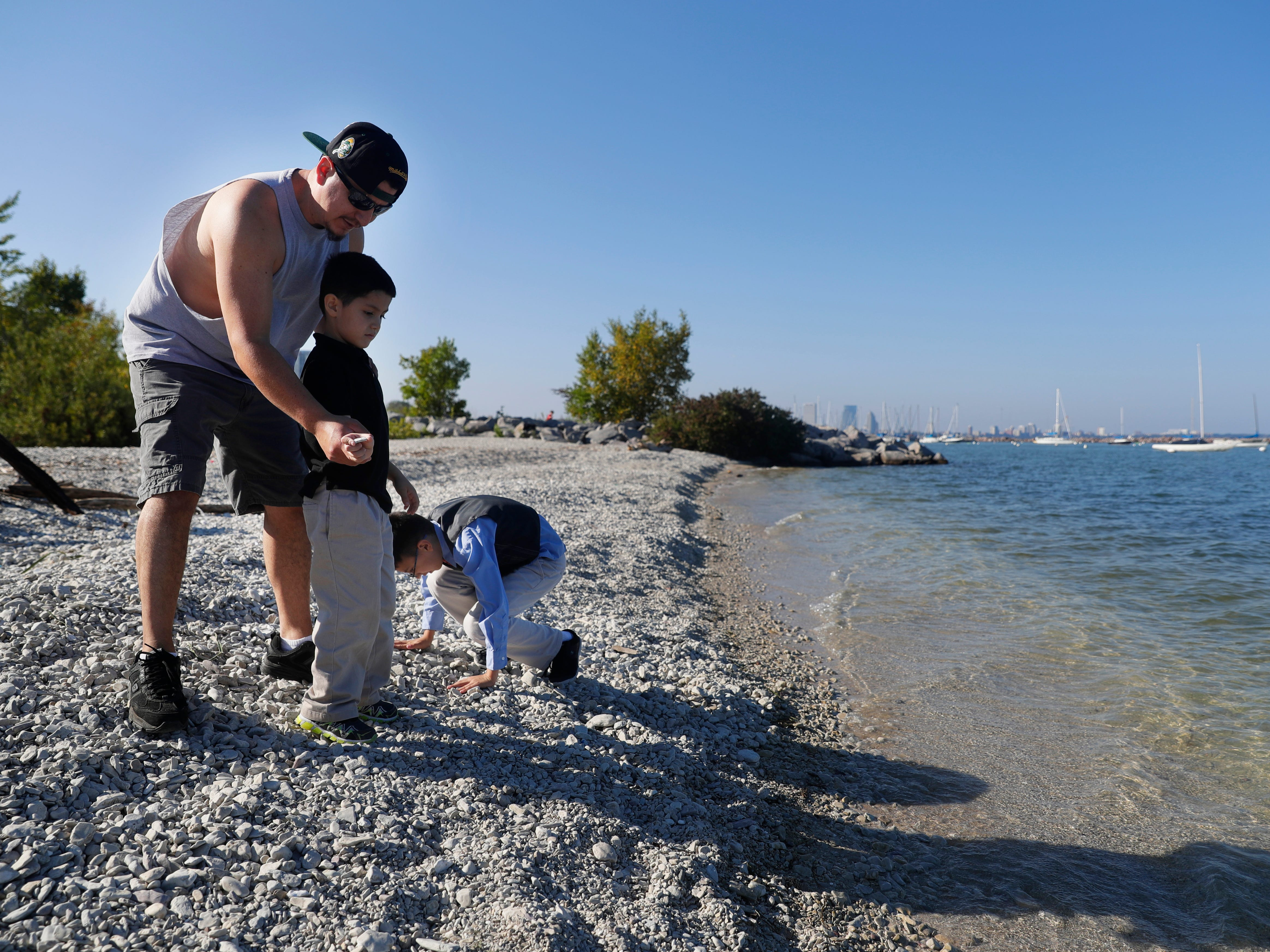 Manuel Canales (left) shows his son, Victor, 6, how to skip a stone over the surface of Lake Michigan at South Shore Park while his son, Christian, 10, looks for more stones toskip.