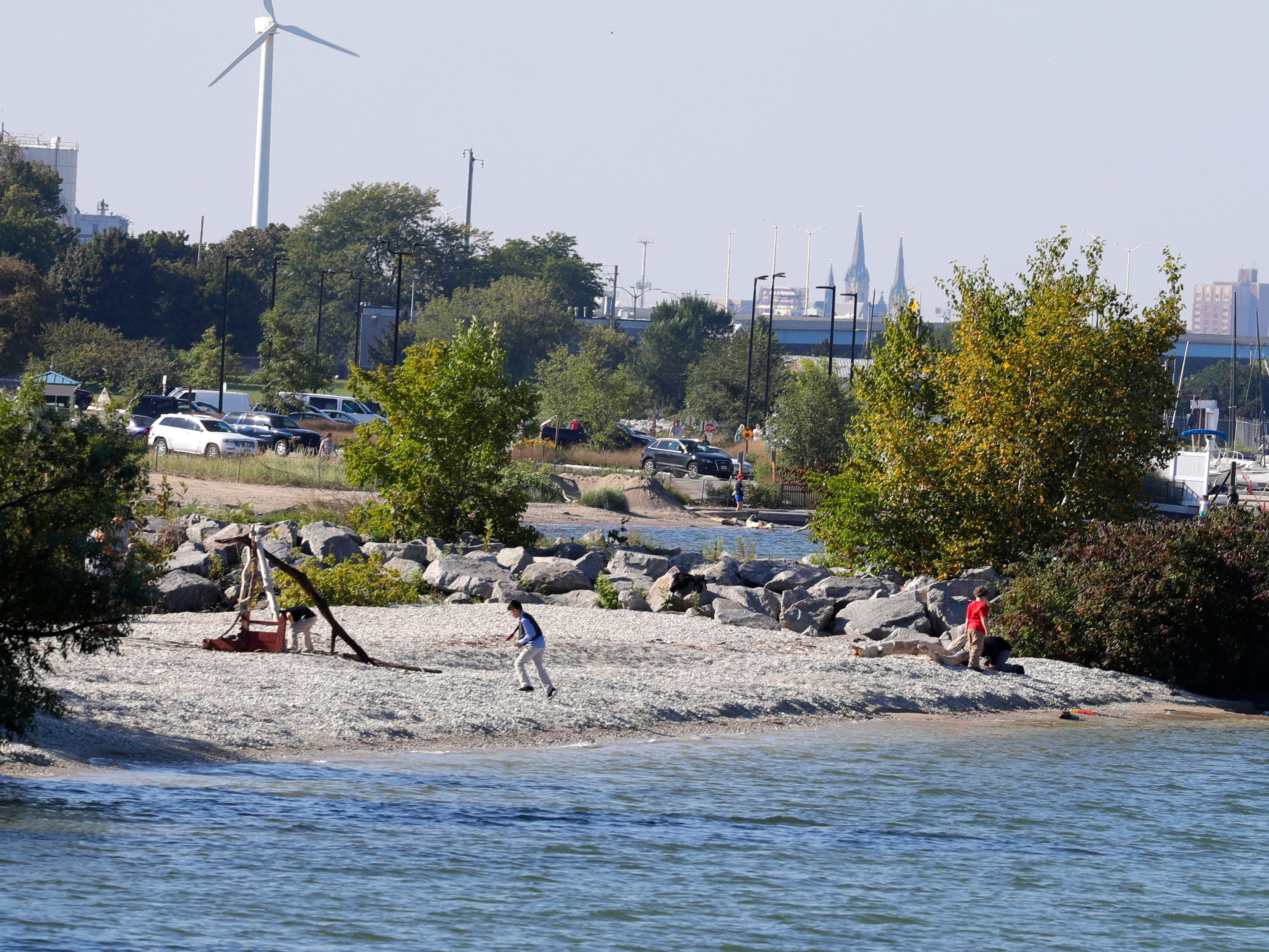 Children play on a stone shoreline south of a jetty (right) at South Shore Park. This stretch of shoreline is one of the proposed locations for a new sand beach for the park.