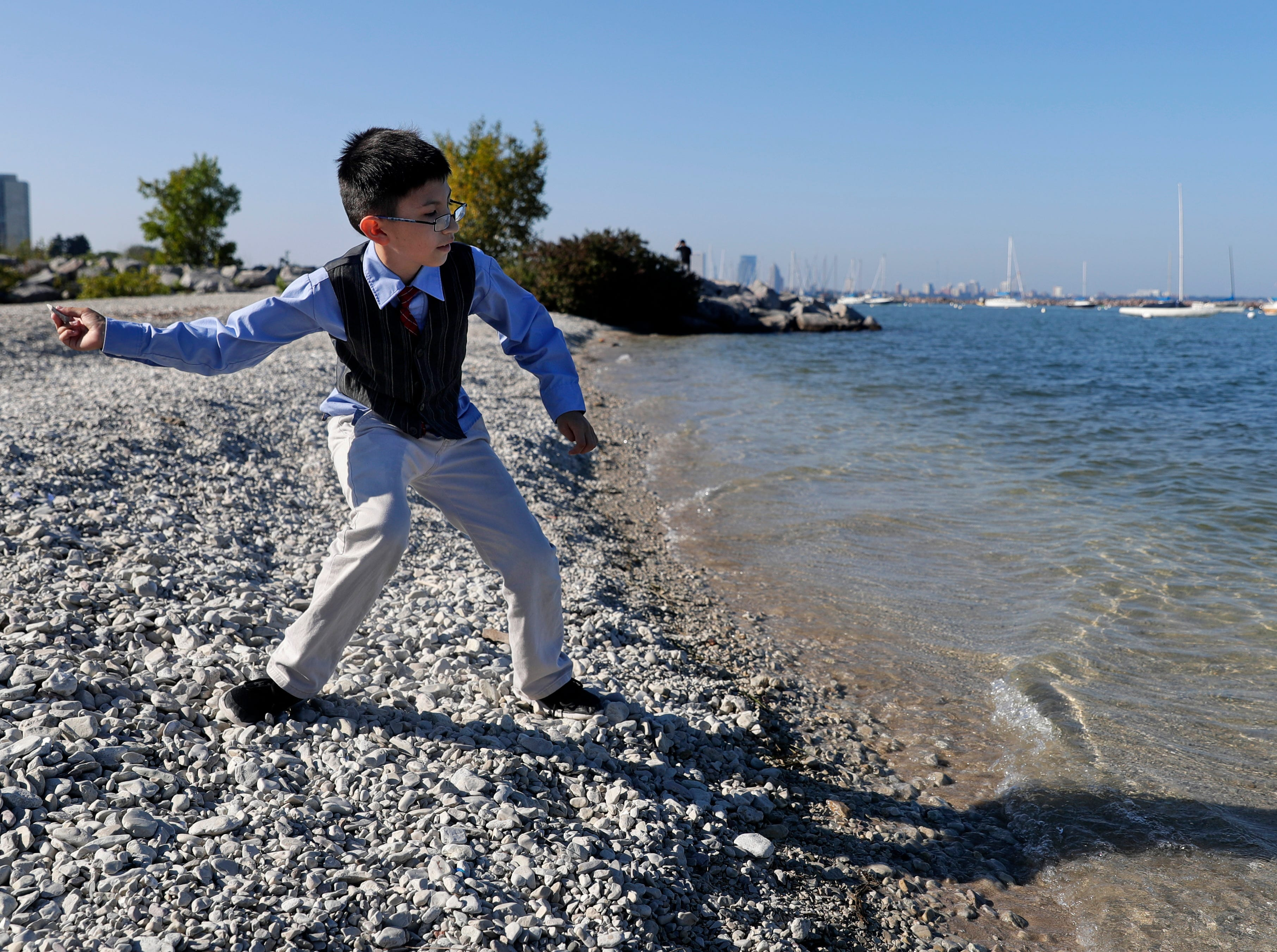 Christian Canales, 10, skips stones along one of four proposed new beach locations at South Shore Park.