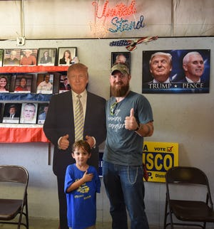 Jeremy and 5-year-old Hunter Hodges of Mountain Home pose with a cardboard cutout of President Donald Trump on Friday afternoon at the Baxter County Fair.