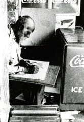 Self-taught artist Bill Traylor at work on Monroe Street in Montgomery around 1939.