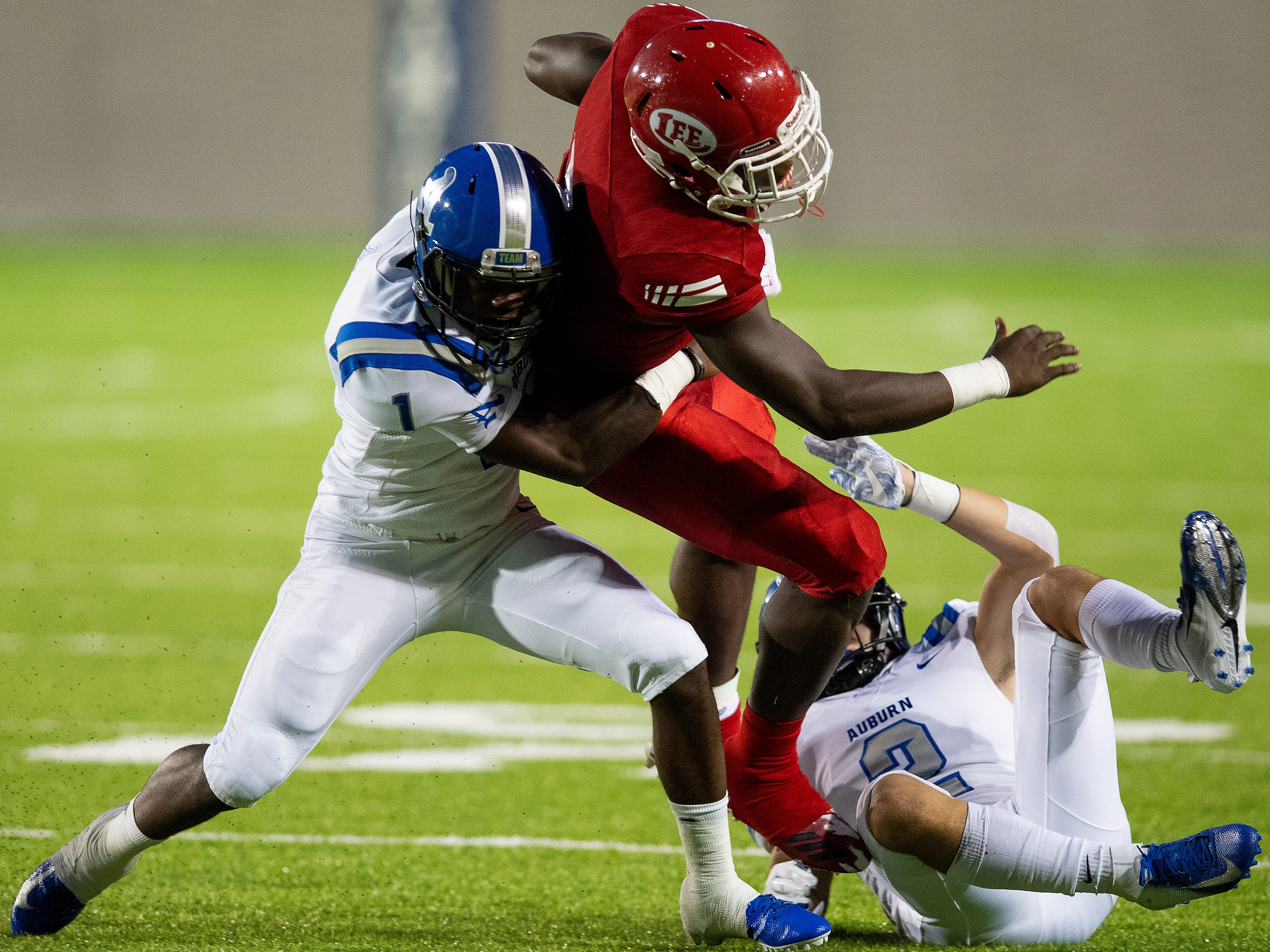 Lee's Tedarrian Murray is stopped by Auburn's JT Rogers (1) and Cally Chizik (2) in first half action at Cramton Bowl in Montgomery, Ala., on Thursday September 13, 2018.