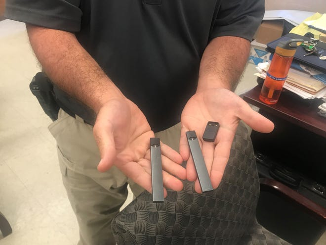 School Resource Officer Chris Gilmore holds a JUUL electronic cigarette.