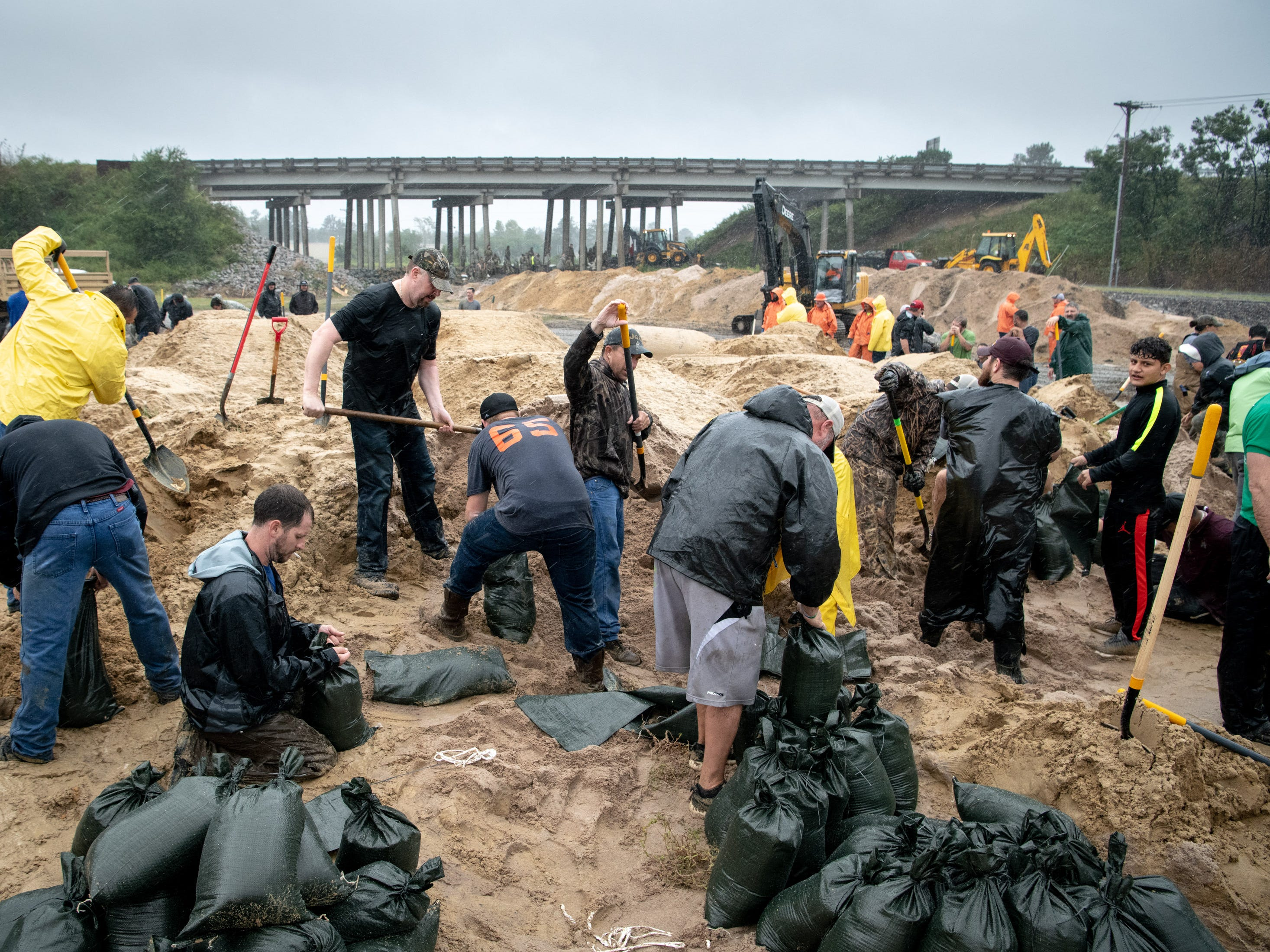 Volunteers fills sandbags to reinforce a low-lying area as Hurricane Florence approaches Lumberton, N.C., Friday, Sept. 14, 2018.
