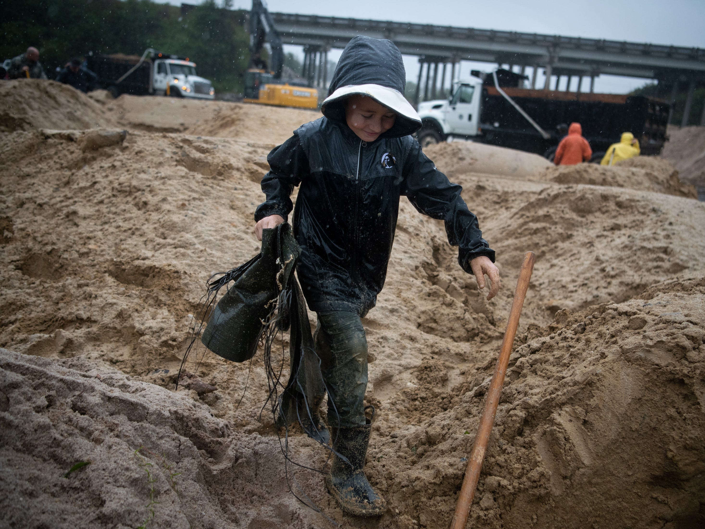 Volunteer Rivers Malcolm, 9, carries empty sandbags for other volunteers to fill as they reinforce a low-lying area as Hurricane Florence approaches Lumberton, Tenn., N.C, Sept. 14, 2018.