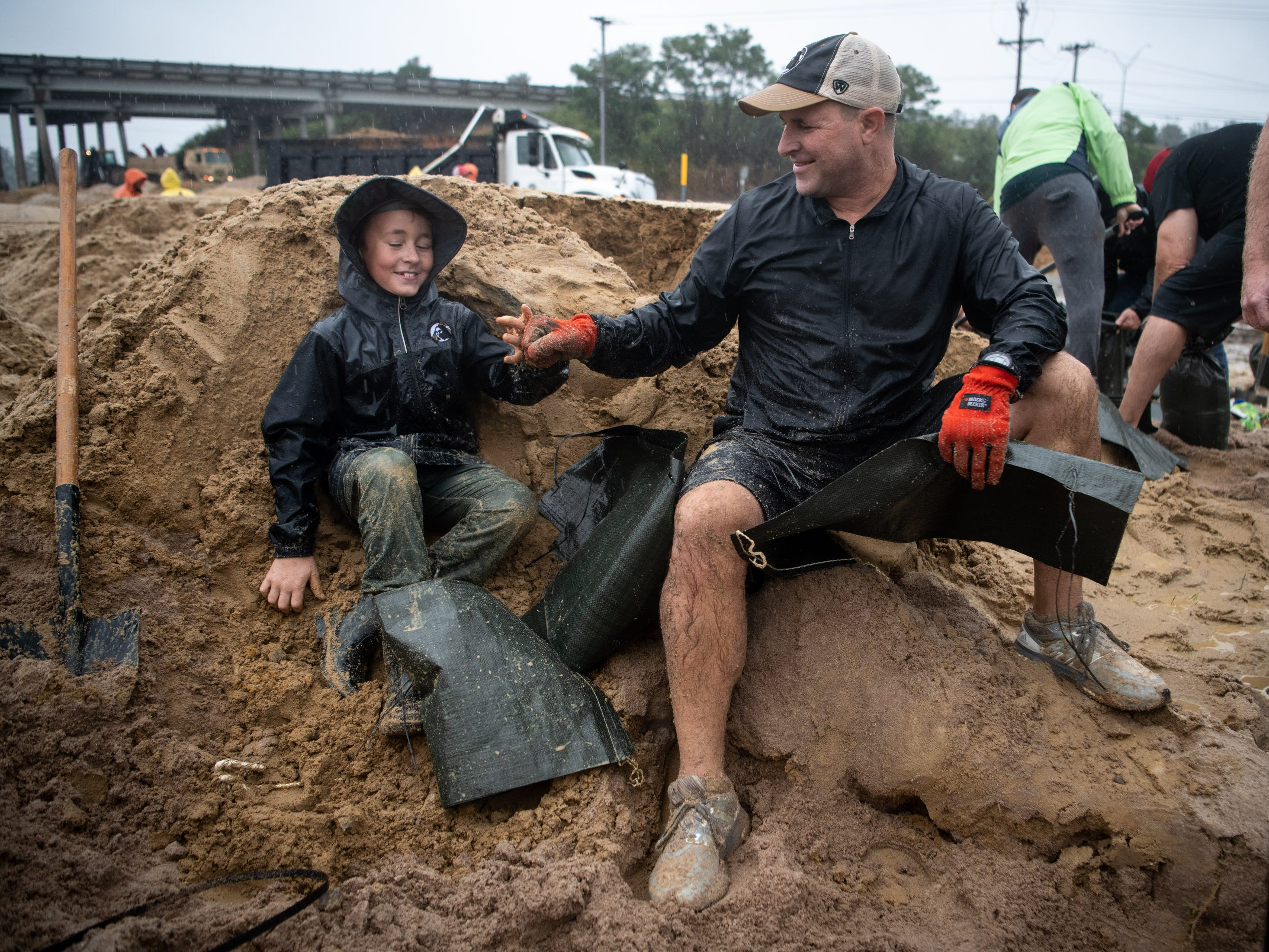 Volunteers Rivers Malcolm, left, 9, and Ben Miller, right, bump fists while filling sandbags to help reinforce a low-lying area as Hurricane Florence approaches Lumberton, N.C., Friday, Sept. 14, 2018.