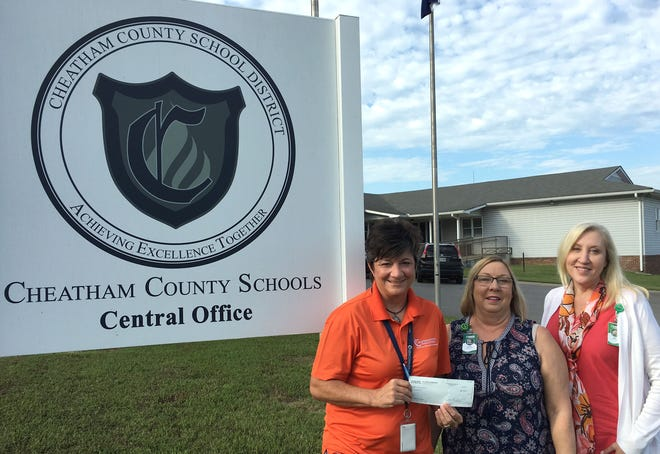 Dr. Tara Watson, the district's Chief Operations Officer, accepts the check from Lisa Williams and Tonya France of A.O. Smith.