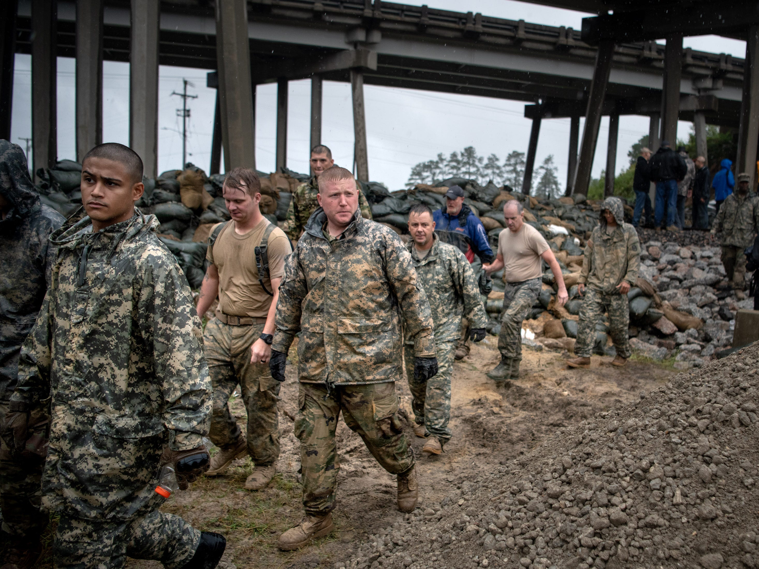 Soldiers from the North Carolina National Guard depart after reinforcing a low-lying area with sandbags as Hurricane Florence approaches Lumberton, N.C., Friday, Sept. 14, 2018.