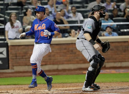 New York Mets' Jeff McNeil (68) runs past Miami Marlins catcher Chad Wallach to score on a two-run double by Michael Conforto during the fifth inning of the second baseball game of a doubleheader Thursday, Sept. 13, 2018, in New York.