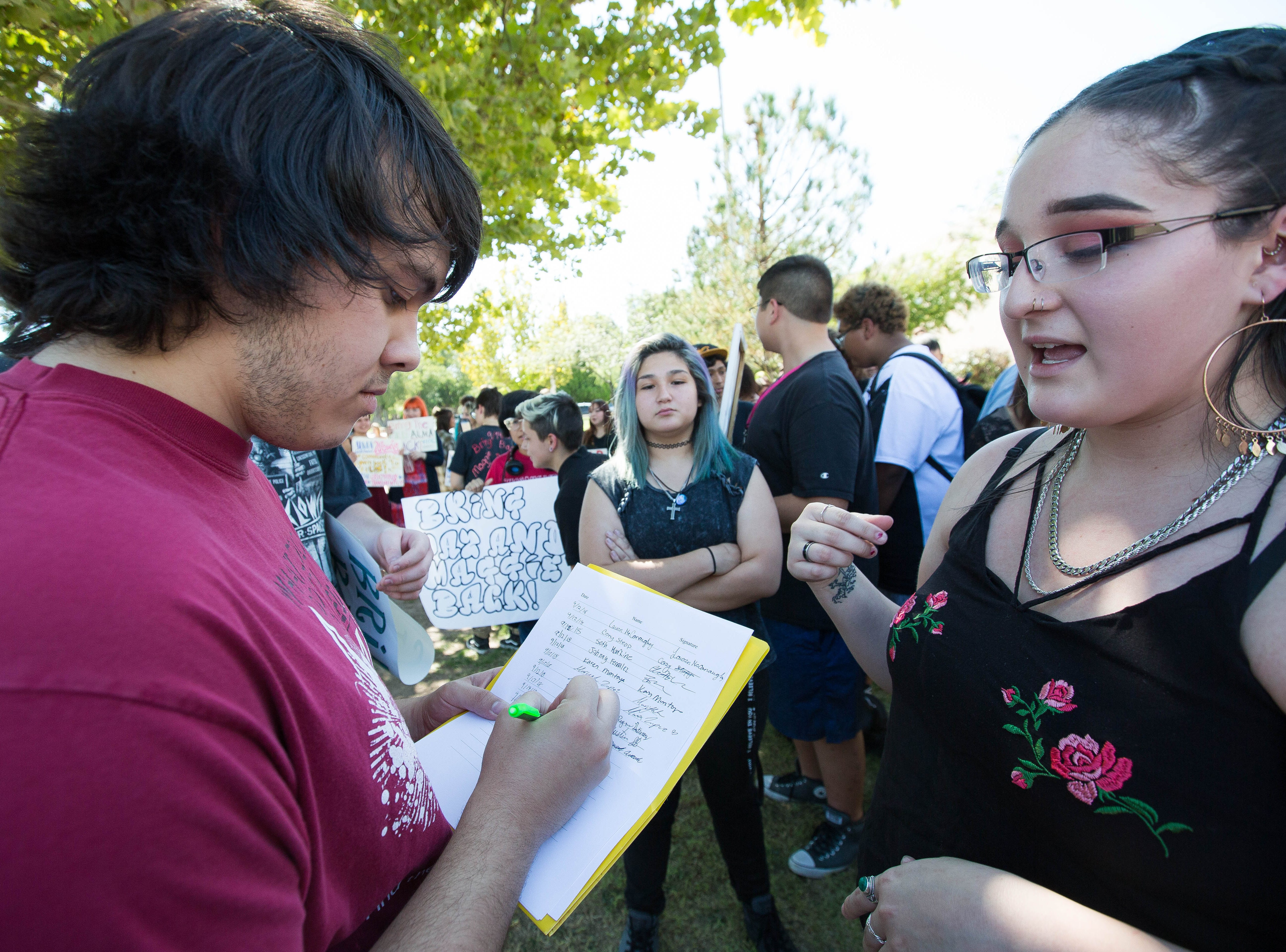 Haley Gillis, 16, right, collects a signature from Eric Lopez, 17 on a petitionduring a student lead  protest at Alma d'Arte over the termination of two  staff, a teacher and a special education coordinator, along  with some student expulsions,