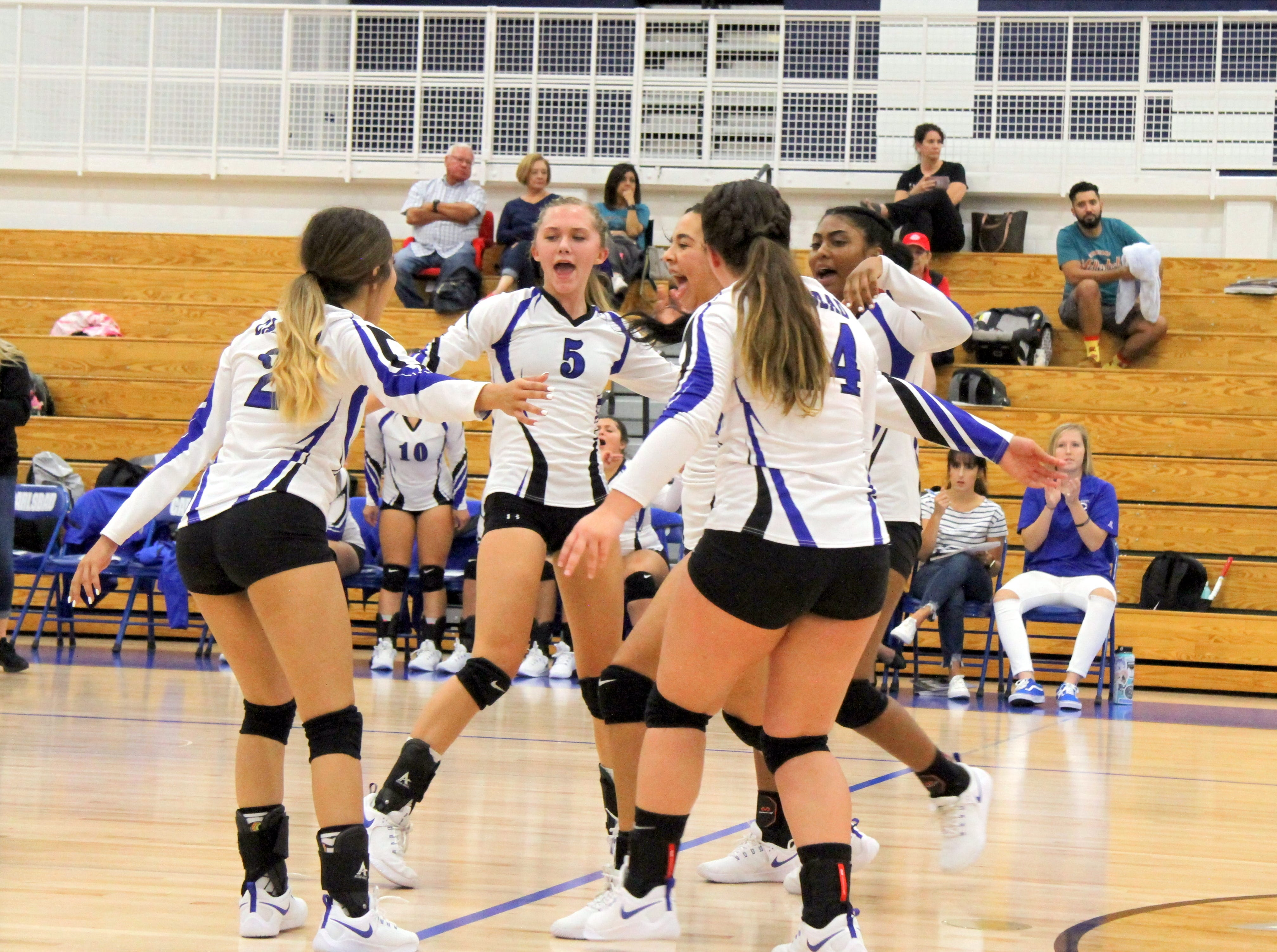 The Cavegirls celebrate a point in the fourth set of Thursday's match against Pebble Hills.