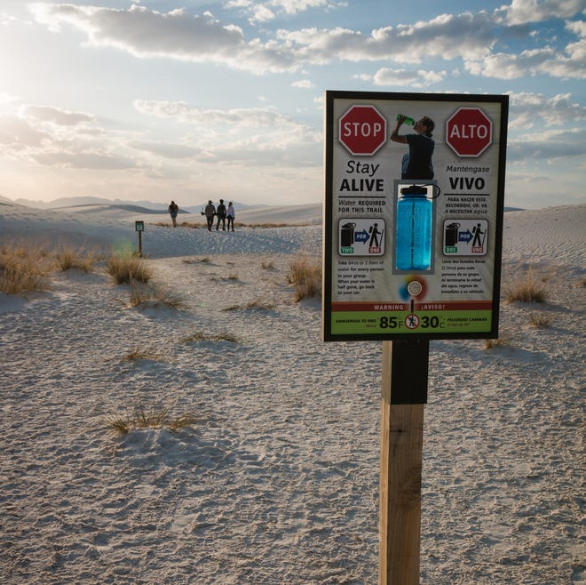 A sign informs White Sands National Monument hikers about taking enough water while hiking on trails.