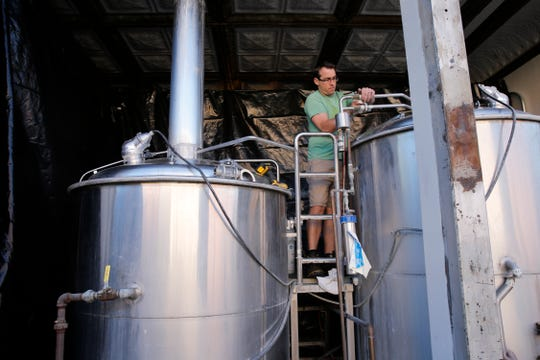 Head brewer Patrick Liessmann works to disassemble the old tanks Thursday at the Three Rivers Eatery and Brewhouse in Farmington.