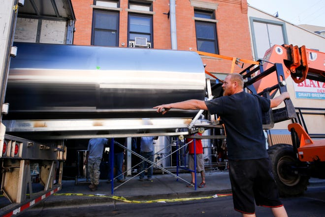 Three Rivers Eatery and Brewhouse maintenance worker Sham Hawkins helps unload the brewery's new hot tank Thursday in Farmington.