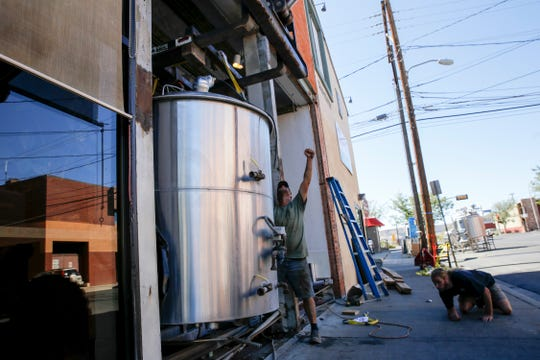 Three Rivers Eatery and Brewhouse employee Mike Ponder, left, and assistant brewer Austin Jacobs remove the brewery's old mash tank Thursday at the brewery in Farmington.
