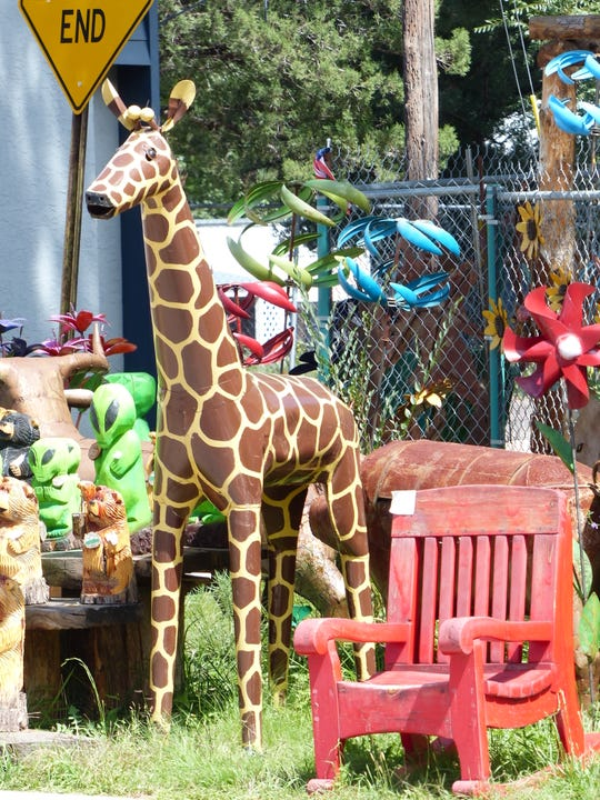 A metallic giraffe adds color of a different kind to the village.