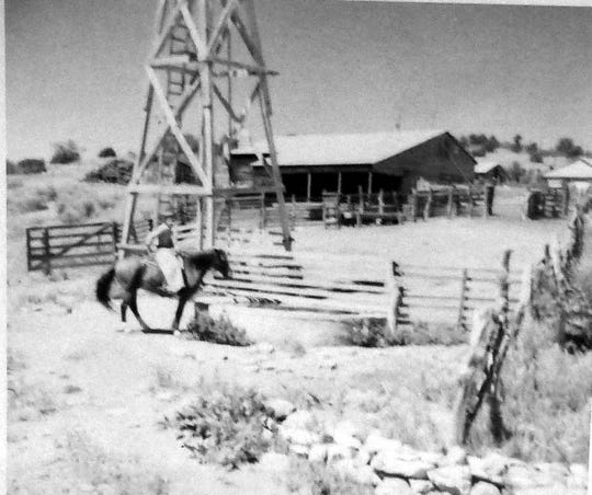 Tom Gould rides a horse in front of the barn still standing on the Followed Dream Ranc