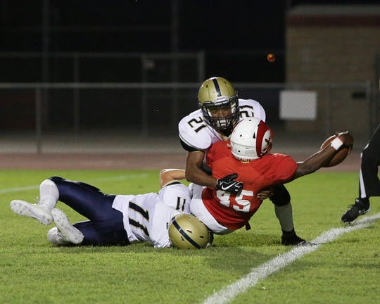 Desert Mirage running back Manny Ridge (45) reaches over the end zone for one of his four first-half touchdowns as Desert Hot Springs' Dylan Kelly (11) and Robert Noriega Jr (21) try to make a tackle on Sept. 13, 2018.