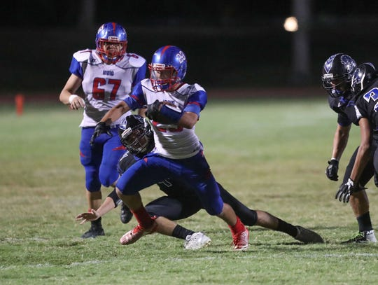 Indio's Victor Hilario runs for a first down against Indio, September 13, 2018