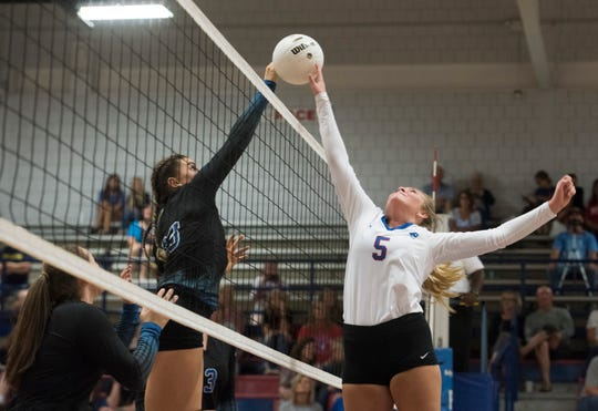 Washington High School's Hailey Jester, (No. 13) and Pace High School's Grace McCammon, (No. 5) battle at the net during match play Thursday, Sept. 13, 2018. The Patriots defeated the Wildcats, 25-8, 26-24, 25-14.