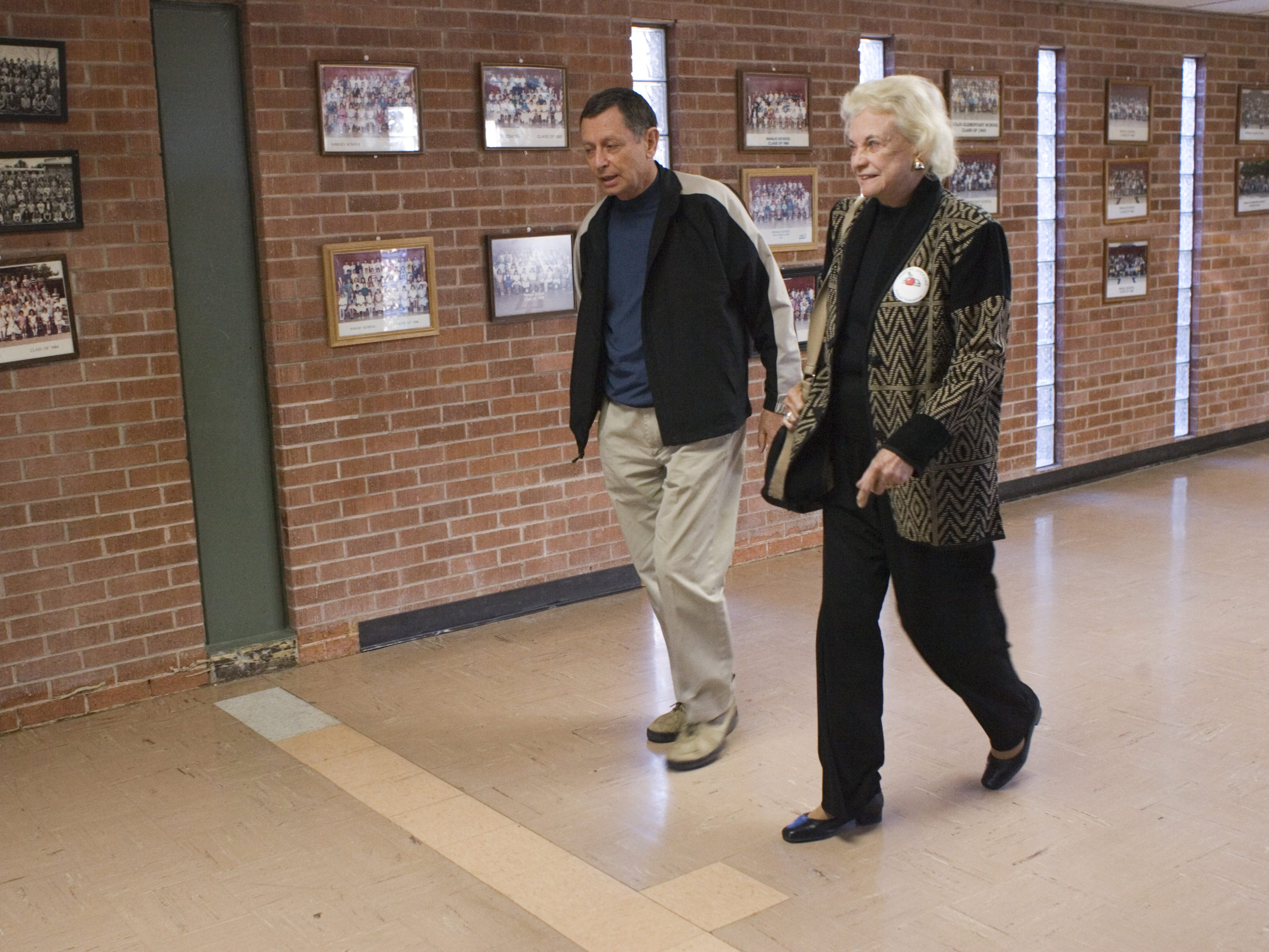 Founder of the Navajo Volunteer Literacy Program,  Dr.  Fred Christensen  walks his friend, Sandra Day O'Connor down the hall of Navajo Elementary School, after she volunteered her time, helping a child read on Jan. 16, 2007.