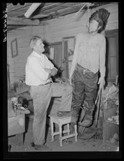 In a May 1940 photo, Homer Tate admires his hanging man. The artist was known for his off-kilter creations.