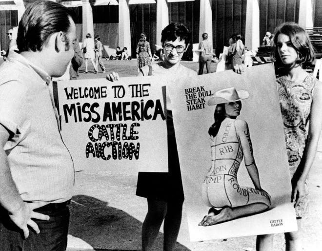 Members of the National Women's Liberation Party hold protest signs in front of Convention Hall where the Miss America Pageant was held in Atlantic City, N.J. on Sept. 7, 1968.  The picketers, also seen behind, protested the annual pageant as degrading to women.