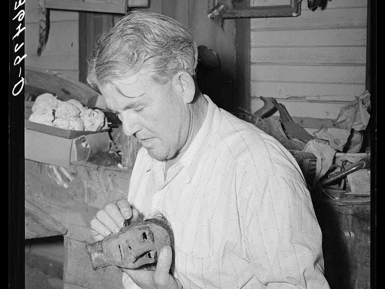 Homer Tate fashions a shrunken head, one of his artist's specialties, in this May 1940 photo.