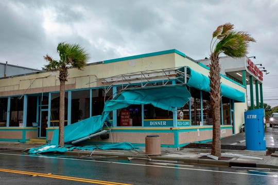 Storm damage caused by high winds is seen on Ocean Avenue as the outer bands of Hurricane Florence make landfall on September 14, 2018 in Myrtle Beach, South Carolina. - Florence smashed into the US East Coast Friday with howling winds, torrential rains and life-threatening storm surges as emergency crews scrambled to rescue hundreds of people stranded in their homes by flood waters. Forecasters warned of catastrophic flooding and other mayhem from the monster storm, which is only Category 1 but physically sprawling and dangerous. (Photo by Alex Edelman / AFP)        (Photo credit should read ALEX EDELMAN/AFP/Getty Images)