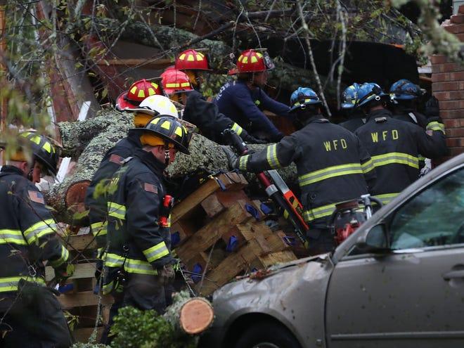 Los bomberos intentan obtener acceso a 3 personas en un hogar que un gran árbol cayó después de que el huracán Florence azotara la zona, el 14 de septiembre de 2018 en Wilmington, Carolina del Norte. Un hombre fue sacado de la casa en estado crítico y se desconoce la condición de otros dos.
