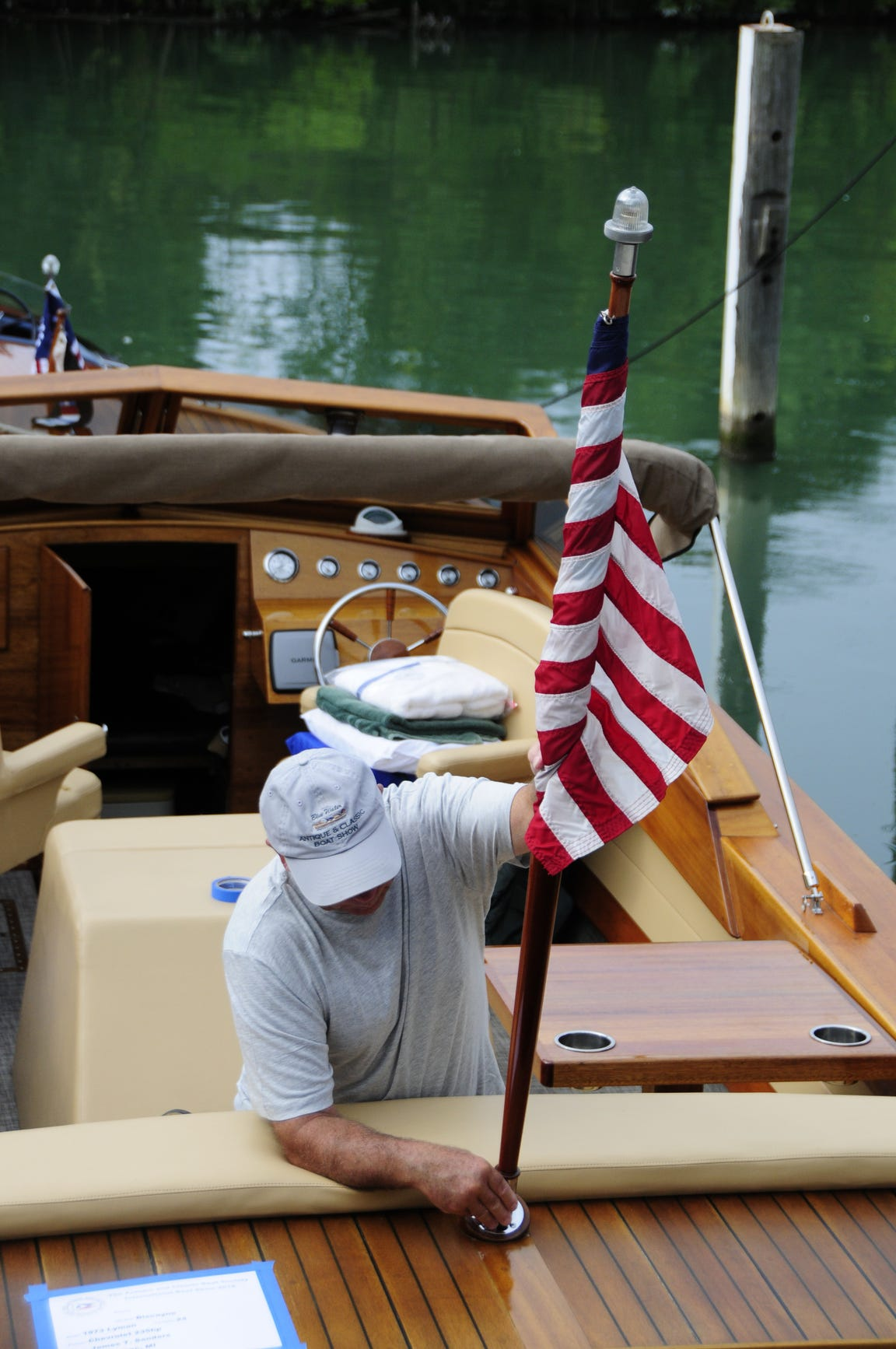 Jim Sanders of Algonac places an American flag at the stern of his 1973 Lyman Biscayne skiff on Friday, Sept. 14, 2018 at the Antique and Classic Boat Society's International Boat Show.