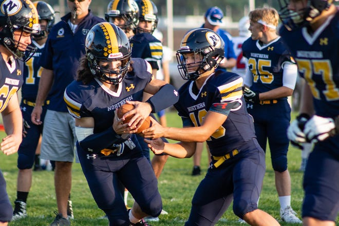 Port Huron Northern running back Theo Ellis takes a handoff from quarterback Seth Klink during a warmup drill  Friday Sept. 14, 2018 at Memorial Stadium.