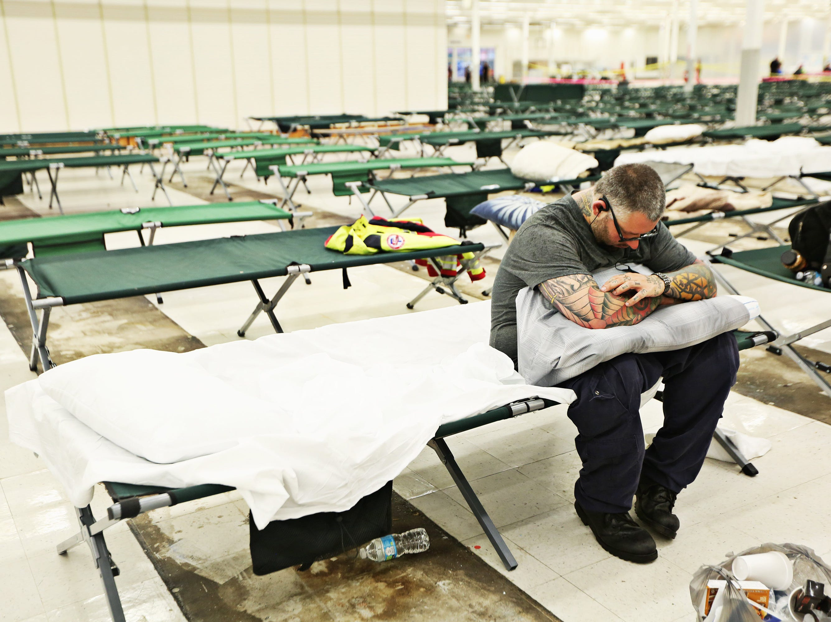 Raffi Hovsepian, a critical care paramedic with All County Ambulance, plugs in earbuds and tries to relax Friday morning, Sept. 14, 2018, in an old Kmart in Garner used as a makeshift shelter for first responders traveling to the state from other areas to wait for assignments to help with Hurricane Florence. Hovsepian travelled with a crew of four men from Ft. Pierce, Fla. (Juli Leonard/The News & Observer/TNS)