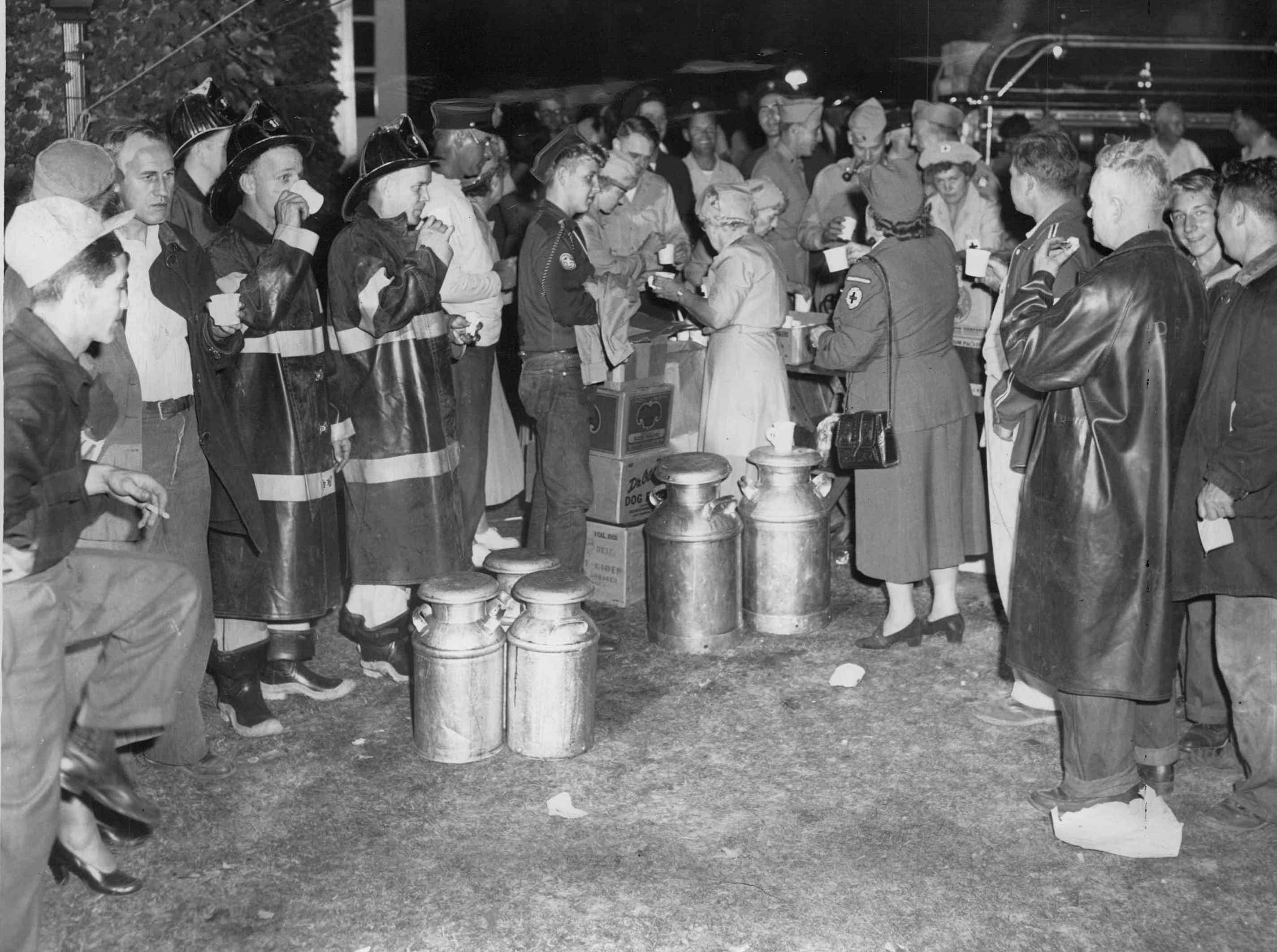 Red Cross aides pass out coffee, sandwiches to firemen, civil defense personnel and other volunteers at scene of Brighton explosions. (Staff photo, 9/21/1951)