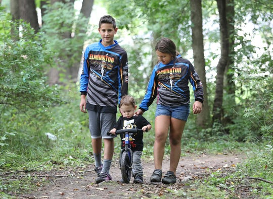 AJ Amico, 10, and his sister Nina Amico, 8, hold onto their one-year-old brother Dominic at their BMX track at their house in Webster.