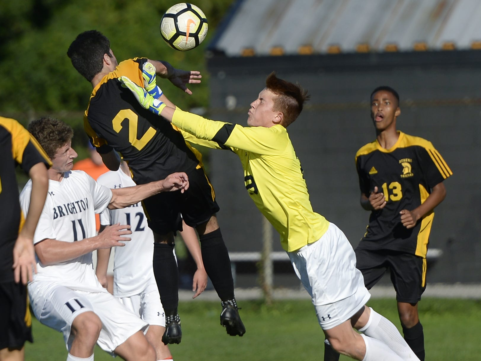 Brighton goalie Christian Burkhart dives to punch the ball away from Greece Athena's Ryan Burns (2) during a regular season game played at Greece Athena High School, Thursday, Sept. 13, 2018. Greece Athena beat Brighton 1-0.