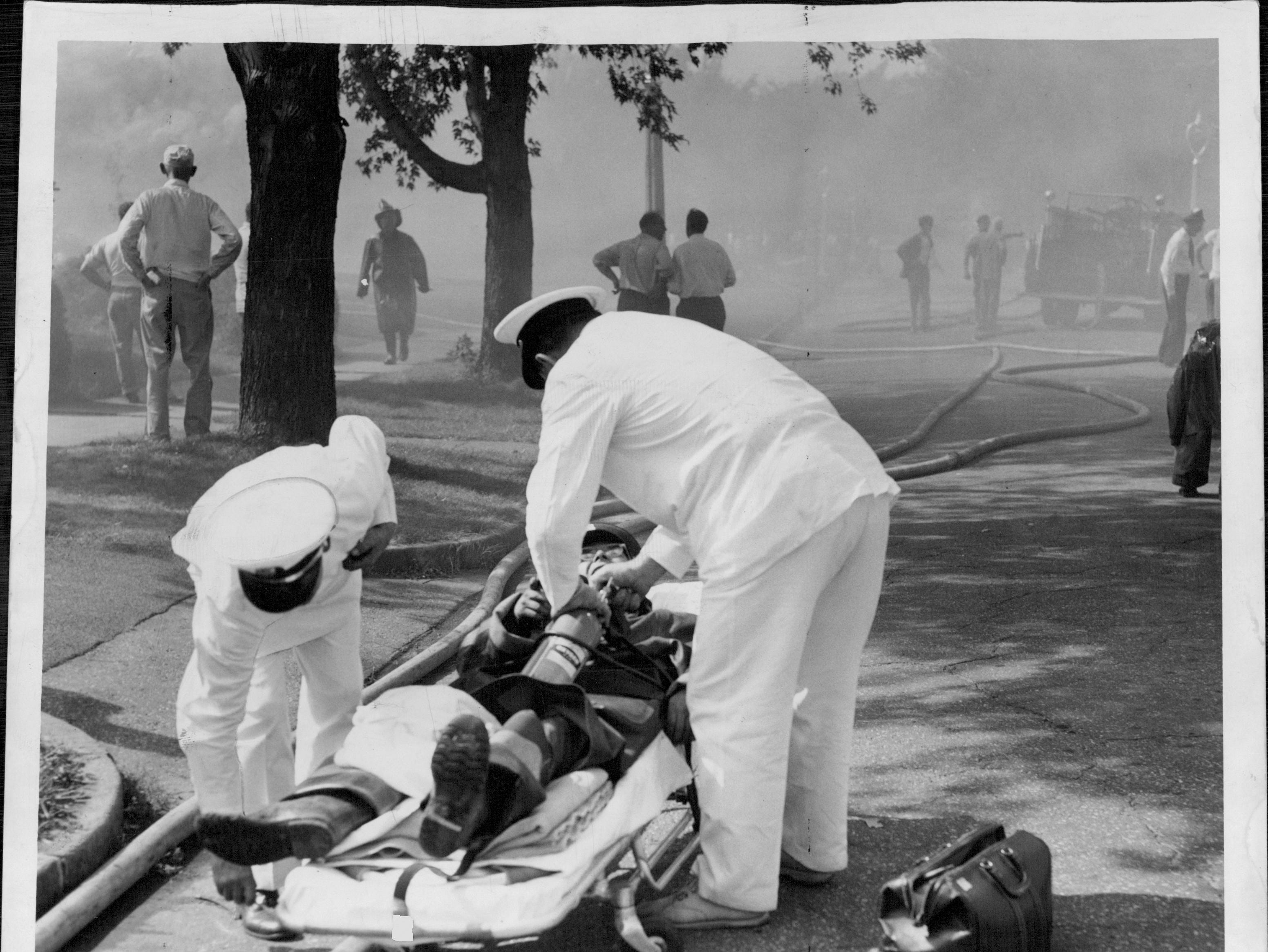 Ambulance crew tends to an injured person. (Staff photo, 9/21/1951)