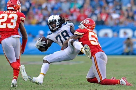 Los Angeles Chargers running back Melvin Gordon (28) is tackled by Kansas City Chiefs linebacker Anthony Hitchens (53).